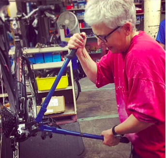 Gwen replacing rear wheel on bicycle at Cornell Outdoor Education bike maintenance clinic
